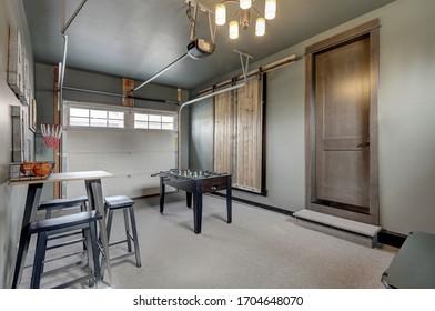 Interior moderno de garaje con divertida sala de juegos familiar con mesa de hockey.