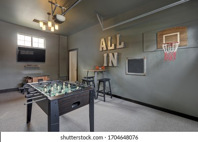 Modern garage interior with fun family play room with hockey table.