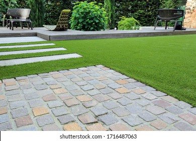 Modern garden design and terrace construction with a material mix of cobble paving stones and concrete paving slab and artificial lawn and wood