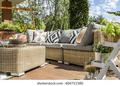 Modern garden patio with comfortable rattan sofa and small table