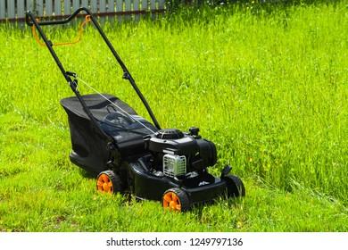 Modern gasoline powered grass mower stands on fresh green lawn in summer garden