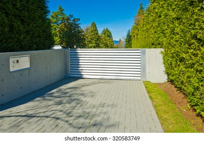 Modern gates with nicely paved driveway. driveway. North America.