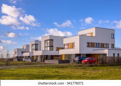 Modern geometric family houses along a green modern residential suburban street, Groningen, Netherlands