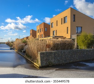 Modern geometric family houses along a river in winter with snow and ice, Groningen, Netherlands
