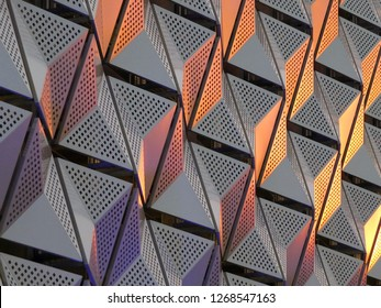 modern geometric triangular shiny silver steel cladding with highlights in gold and copper tones and perforated design