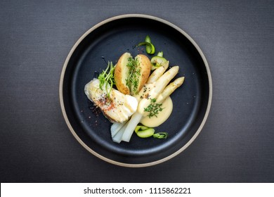 Modern German fried cod fish filet with white asparagus in hollandaise sauce und roast potatoes as top view on a plate with copy space
