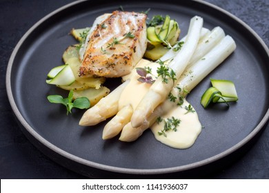 Modern German fried cod fish filet with white asparagus in hollandaise sauce with roast potatoes and sliced zucchini as top view on a plate