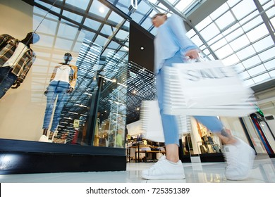 Modern girl looking for trendy clothes on black friday sale while shopping in trade center