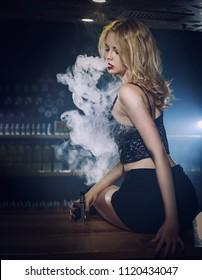Modern girl smoking vape.Trendy new vaping device,smoke e-liquid instead of nicotine cigarettes.Tobacco free e-juice. Vaping concept