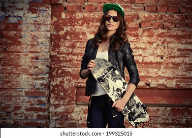 Modern girl teenager stands with skateboard outdoor near the brick wall.
