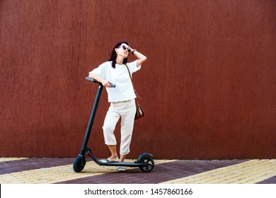 Modern girl in white clothes standing with electric scooter near the wall in street outdoor.