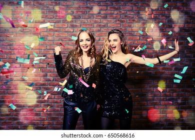 Modern girls having fun on a night party. Celebration, confetti. Christmas party.