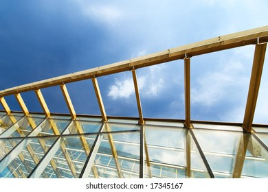 Modern glass bridge over Moscow river with sky reflection
