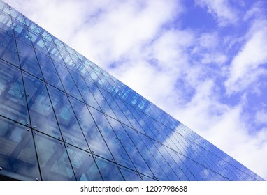 Modern glass building can accommodate offices, apartments, hotel rooms. Cloudy sky  background over skyscraper, space.