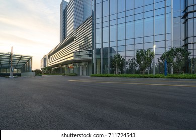 modern glass building with empty asphalt road at twilight,suzhou,china.