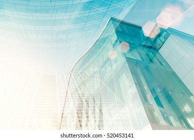 Modern glass building with sun flare. Soft focus of city for abstract background.