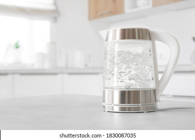 Modern glass electric kettle boiling on kitchen table