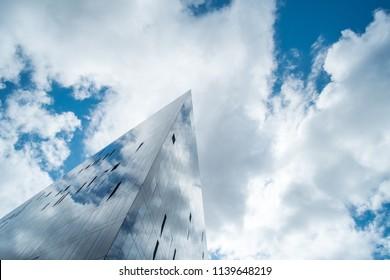 Modern glass facade office building against blue sky