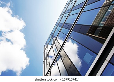 modern glass facade of an office building in which the sky is reflected