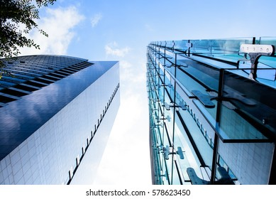 Modern glass office building in the city with cloudy sky reflection on glass wall, low angle view