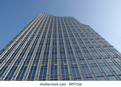 A modern glass office tower rising into the sky