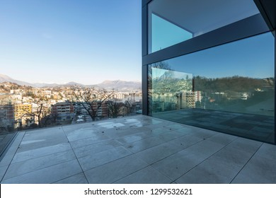 Modern glass palace terrace overlooking the city and Lake Lugano. Sunny day