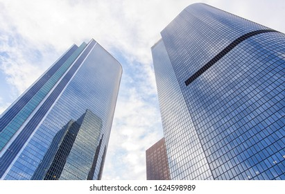 Modern glass skycrapers background with sky and clouds