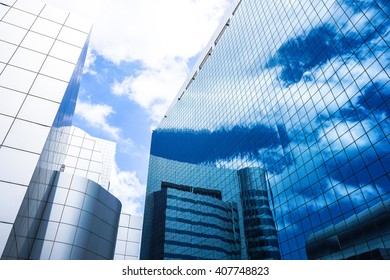 Modern glass skycrapers background with sky and clouds reflection