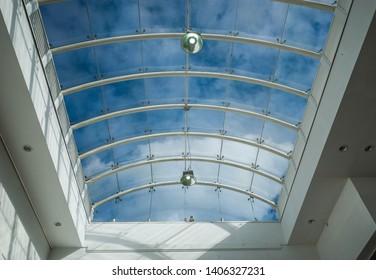 Modern glass skylight ceiling with blue sky background.
