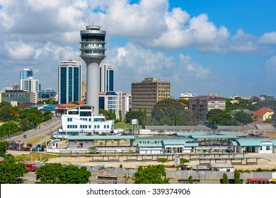 Modern glass skyscrapers stand alongside older buildings in Dar Es Salaam with maritime control tower on foreground