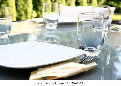 Modern glass table prepared for summer garden party
