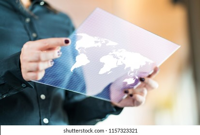 Modern global and international business technology concept. Businesswoman using futuristic transparent tablet with world map on screen. Export, foreign trade and communication concept.