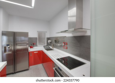 Modern gloss red kitchen with a white seamless kitchen top, breakfast bar and stainless steel appliances.