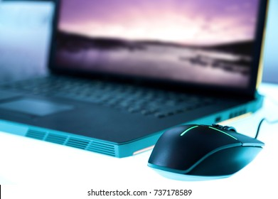 Modern glowing mouse connected to gaming laptop