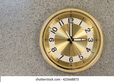 Modern gold clock on marble background.
