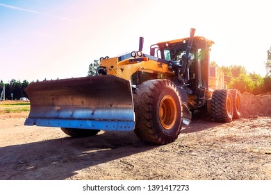 Modern grader in natural conditions at sunset