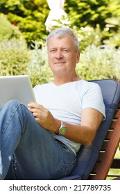 Modern grandfather with digital tablet sitting at home in garden and surfing on net.