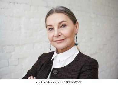 Modern grandmother with wise blue eyes posing indoors, dressed in stylish checkered jacket over white shirt. Beautiful mature woman wearing stylish clothes and accessories isolated at blank wall