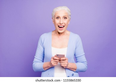Modern granny! Beautiful nice gray-haired excited old lady business woman wearing casual, received winning notification in smartphone. Isolated over pastel violet purple background
