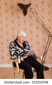 Modern granny enjoys tablet
