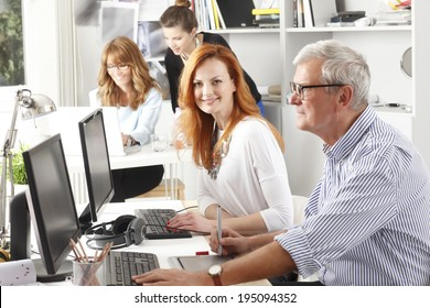 Modern graphic designer woman working with colleagues in office. Small business.
