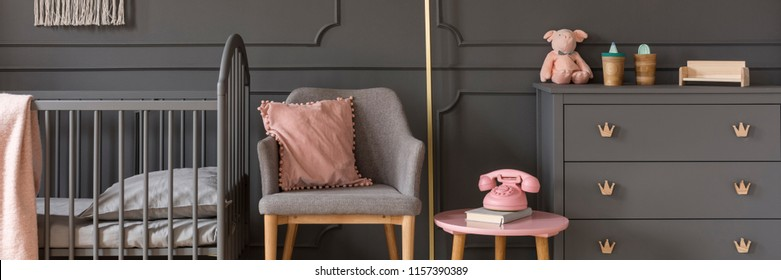 Modern gray armchair by an elegant wall with wainscoting, between a classic, wooden baby crib and a scandi dresser in a dark nursery bedroom interior