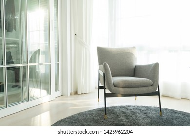 Modern gray armchair and carpet in bedroom in front of big window.