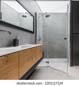 Modern, gray and black bathroom with shower and wooden cabinet
