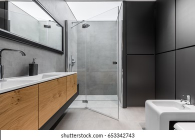 Modern, gray and black bathroom with shower, bidet, sink and wooden cabinet