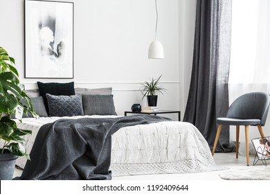 Modern, gray chair with wooden legs by a window of a bright bedroom interior with a dark gray blanket on a comfy bed