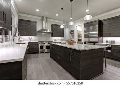 Modern gray kitchen features dark gray flat front cabinets paired with white quartz countertops and a glossy gray linear tile backsplash. Northwest, USA  - Shutterstock ID 557518258