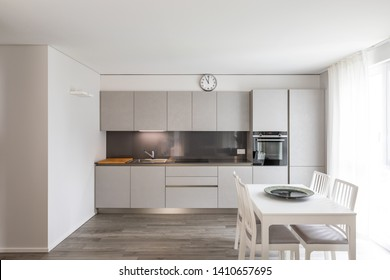 Modern gray kitchen with white chair and table. Nobody inside