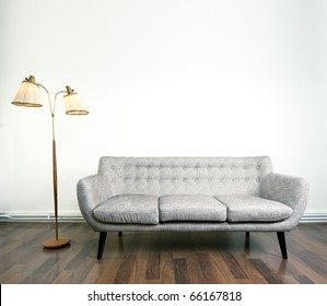 A modern gray sofa and a retro lamp with two heads against bright background on wooden floor