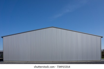 Modern gray warehouse with sheet metal cladding and large roller door